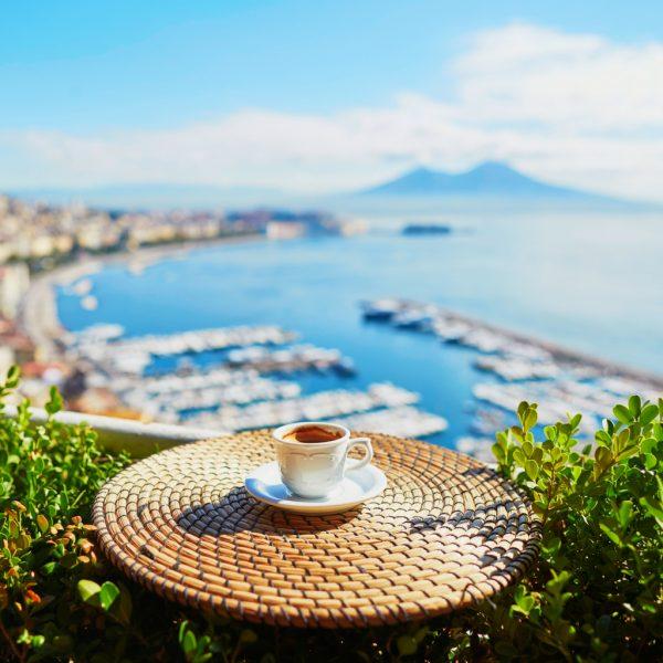 Tazza di caffè con il mare come sfondo e un cespuglio verde ai lati